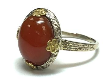Beautiful carnelian cabochon set in a white gold ring with yellow gold floral prongs