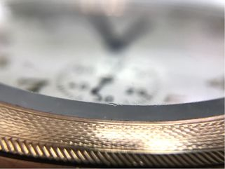 Abrasions along the faceted edge of this glass pocket watch crystal.